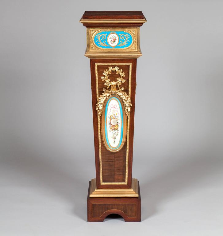A Pair of Pedestals in the Louis XVI Manner  Constructed in harewood, dressed with boxwood line inlays, bleu celeste 'Sèvres' style plaques decorated with foliates and martial trophies, and having bold, finely cast and chased ormolu mounts; rising