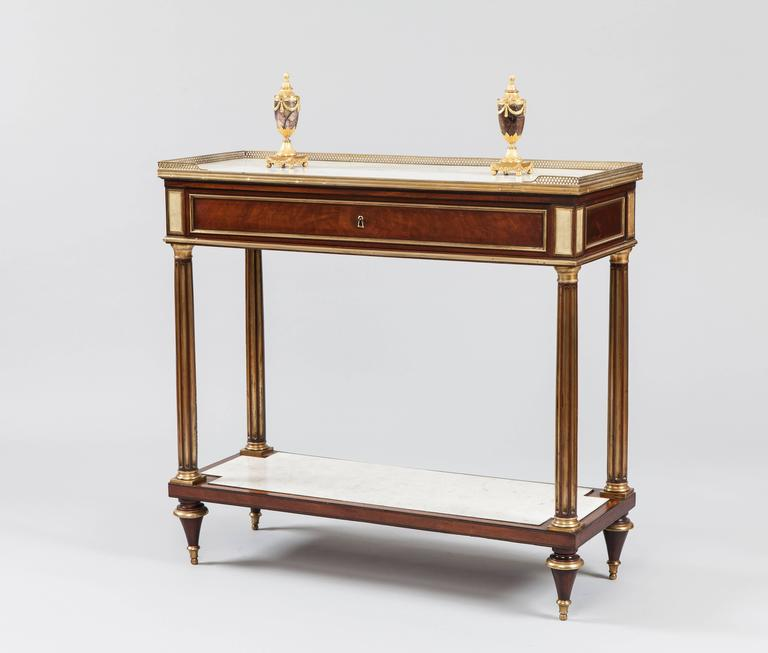 A good console-desserte of the Directoire period.  Constructed in mahogany, having ormolu and brass accents; rising from toupie feet, the lower tier having an inset shaped Carrara marble tablet, the four legs of entasis form with channelling with