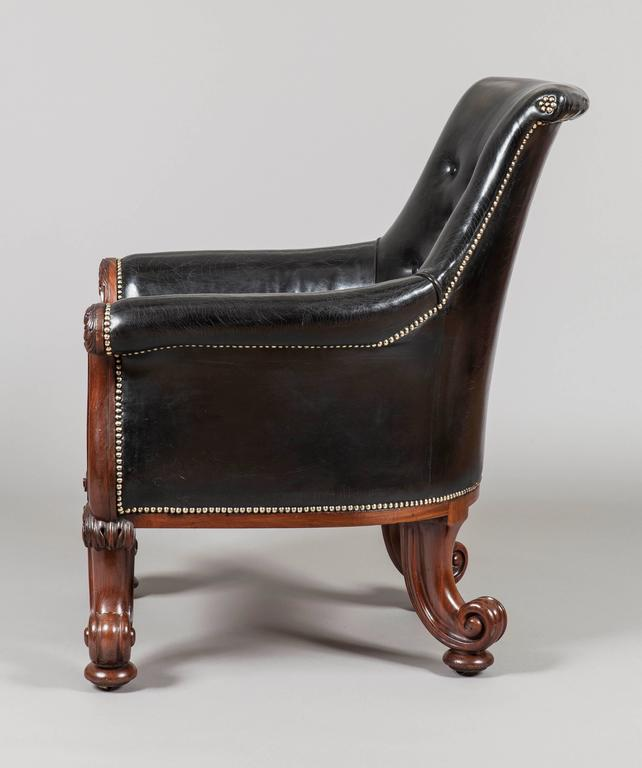 A magnificent pair of George IV library armchairs firmly attributed to Gillows of London and Lancaster  Constructed in mahogany: the front legs of addorsed 'C' scrolls, confidently and exuberantly carved with foliates, conjoined by a boldy reeded