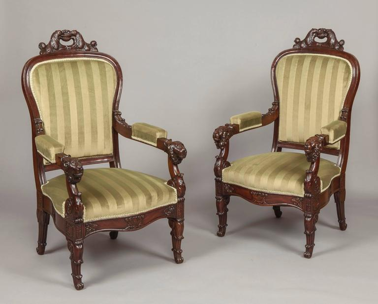 An Imposing Pair of Louis Philippe Fauteuils  Constructed in Honduras mahogany, standing on swept lappeted gentle 'S' shaped legs to the front, and sabre shaped to the rear, the padded arms, leaf carved, terminate in lions heads. The balloon form