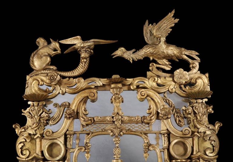 An Irish looking glass in the rococo manner of Thomas Johnson probably by Butler of Dublin  Constructed in carved gold giltwood, the mirror plates housed within a typical exuberant and florid Johnsonian medley of Chinese, naturalistic, symbolic and
