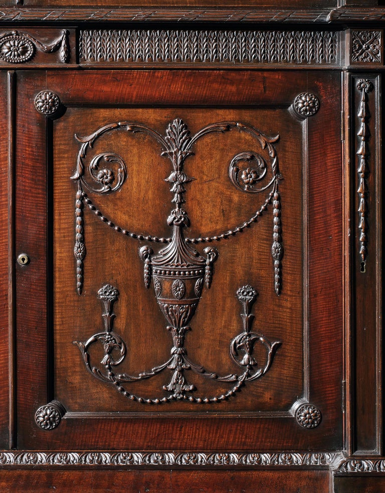 A library bookcase in the manner of the Adam Brothers  Constructed in a well figured mahogany, with fine carved detailing; of inverted four-door breakfront form, rising from a plinth base with a stiff leaf carved ogee edging; the lower section