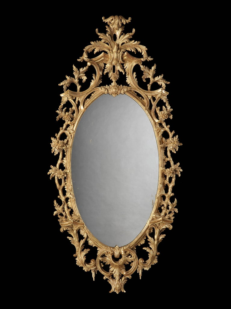 The elliptical mirror plates enclosed by gesso and gold giltwood frames, exuberantly carved with scrolling acanthi, foliates and scrollwork in the Rococo manner, the surmounts having cabochons issuing acanthus spray crests, circa 1880  Graham