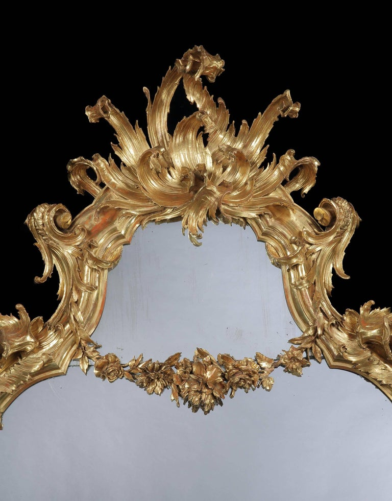 With an elaborately caved gold leaf framed with free scrolling lappet branches in the rococo style, the base with inverted cabriole legs and a central shell and leaf cartouche, the plate divided by a floral garland and the whole surmounted by an