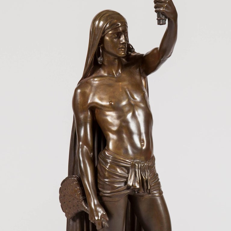 A well patinated bronze figure, representing an American Indian, wearing a draped headdress, robe and a pendant hooped earring. Signed to the plinth 'A.Tossaint 1850', and the foundry, 'Graux-Marly, Fat. de Bronze' France, circa 1850  The