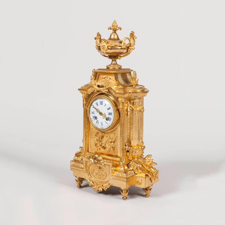 A Garniture de Cheminee by Japy Freres et Cie Constructed in two color gold ormolu, comprising a richly decorated mantle clock and two candelabra in the late Louis XVI manner; the breakfront form clock rising from foliate adorned toupie feet,