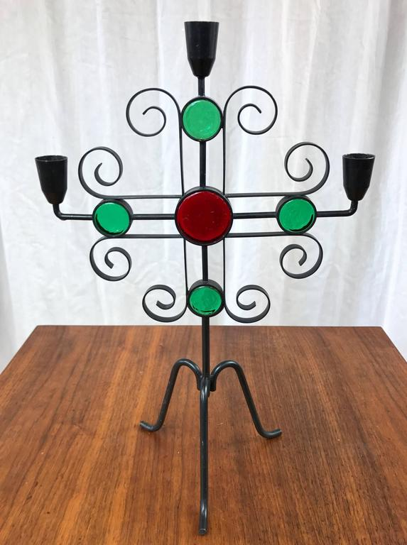 A tall wrought iron candelabra-style candleholder with glass accents by Gunnar Ander for Ystad-Metall.  Its curlicues and vibrant colors represent a delightful Mid-Century Modern interpretation of traditional Swedish design motifs. Finished in
