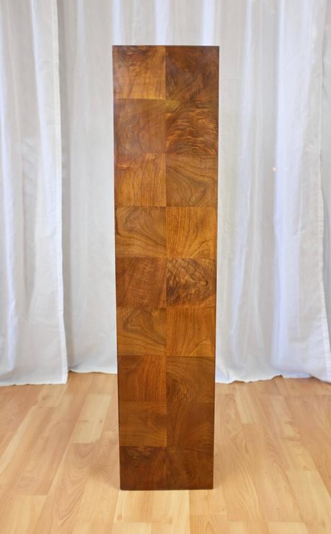 A circa-1970s tall walnut pedestal in the style of Milo Baughman.  Finished on all sides in lively figured crown cut walnut veneer squares with a bright, warm tone. An understated yet stately stage upon which to display a prized piece of art or
