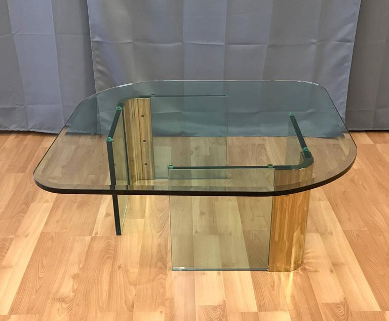 A large and uncommon coffee or cocktail table with brass and glass base and thick asymmetrical glass top that's very much in the style of Leon Rosen's work for Pace Collection.  Base comprised of a pair of free-standing scalloped brass architectural