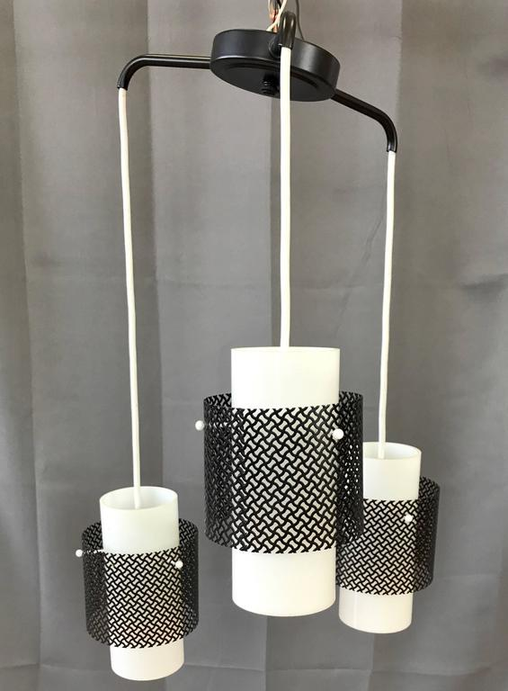 A sharp looking Mid-Century Modern three-light ceiling fixture with glass shades and metal diffusers.  Milk white cylindrical glass shades hang in a staggered arrangement from outstretched black enameled metal arms. Each shade is pierced and