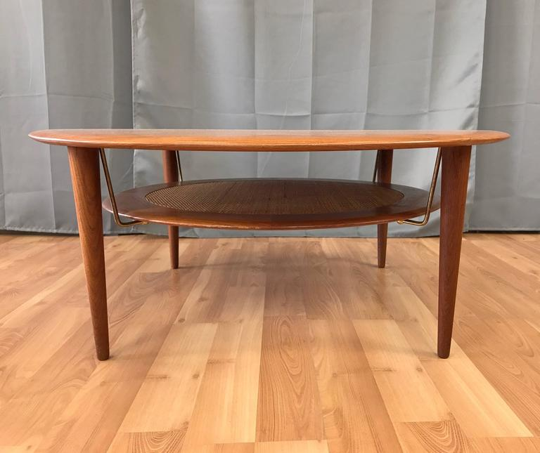Handsomely distilled Danish modern design, with an expansive disc top and tapered legs handcrafted in solid teak. Floating lower tier features a sleek teak ring with original tightly woven rattan inset, and is suspended by four discreet brass rods.