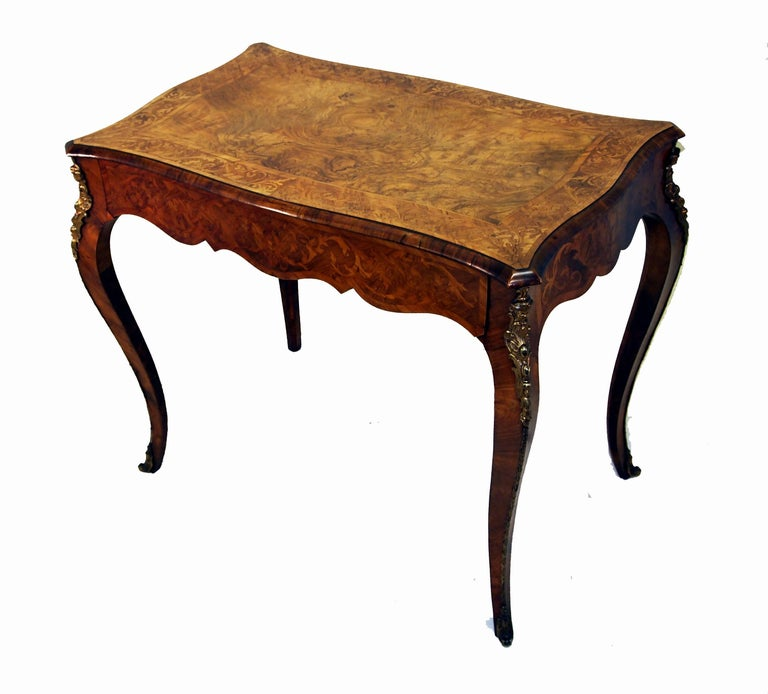 A superb quality Victorian walnut centre table of serpentine Form having one long drawer to shaped frieze and fine ormolu mounts standing on elegant cabriole legs with stunning inlaid decoration.