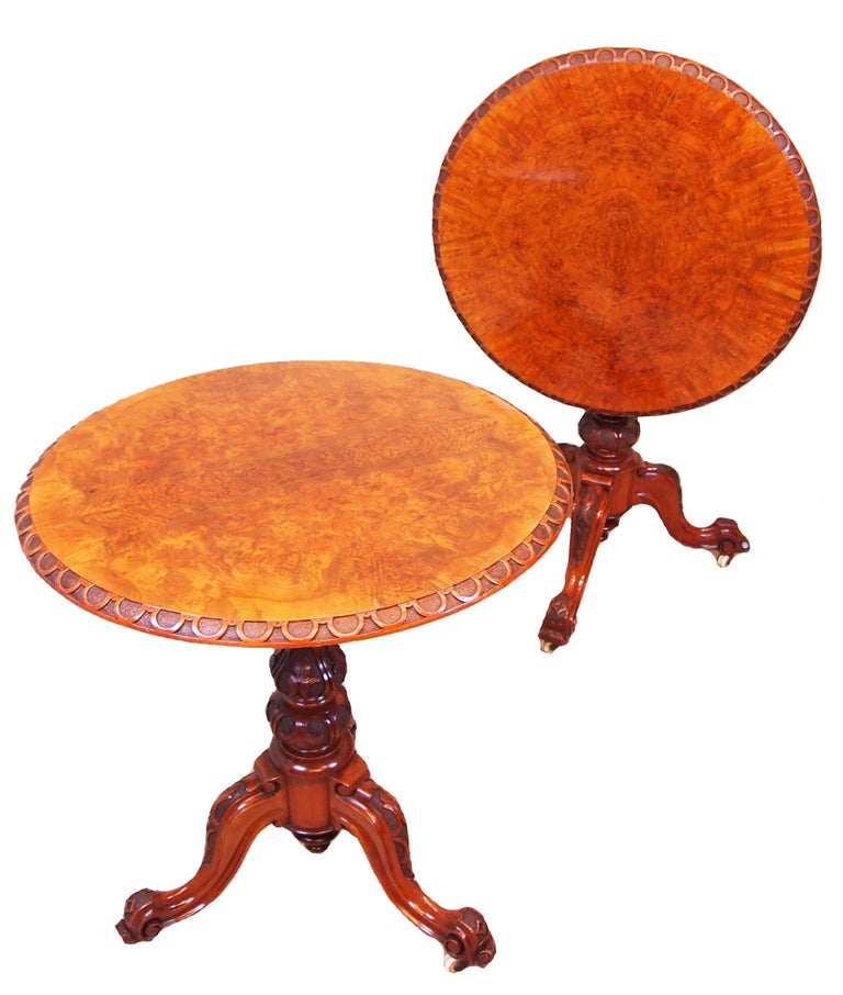 A superb quality and extremely rare pair of mid-19th century burr walnut lamp tables having superbly figured burr walnut circular tops, one tilting, with blind fretwork carved decoration to edges raised on carved central columns terminating on
