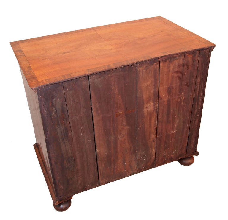 An early 18th century walnut chest having quarter veneered and cross banded top above two short and three long well figured drawers raised on replacement turned bun feet.