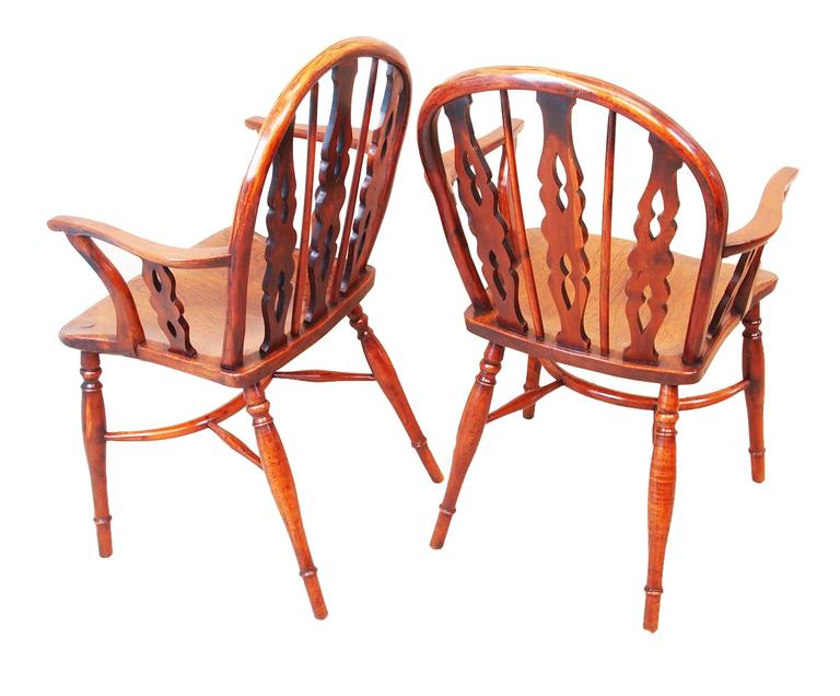 Delightful near matching pair of early 19th century low back. Yew wood Windsor armchairs having three pierced and shaped  splats with central set roundels and alternating spindles above  well figured arms and shaped seats raised on elegant turned