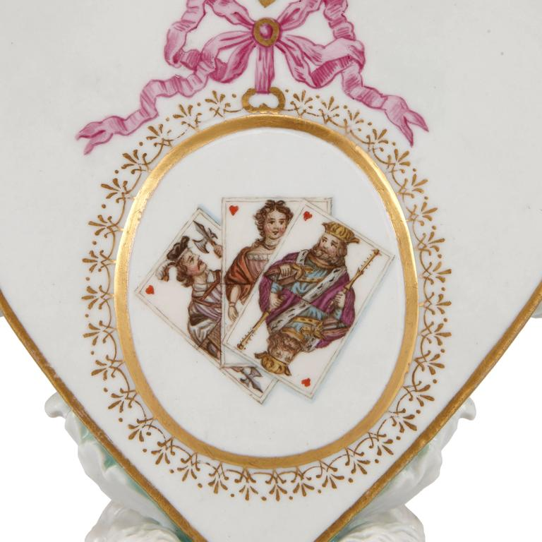 Each candleholder finely detailed to the centre with an image of playing cards to one side and crest on the reverses, each image contained within a gilt circle, further enhanced with gilt pattern work and a pink ribbon, all set within heart shaped