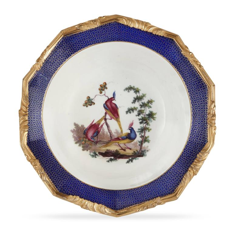 Each porcelain body finely painted to the interior and exterior with polychrome birds and flowers on a white ground, mounted with a thick ormolu rim and all situated on a scroll leaf ormolu base.
