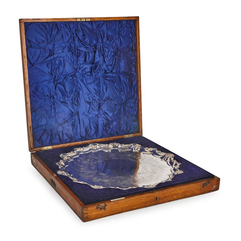By Dobson & Sons (London, est. 1877), retailed by Elkington & Co. Ltd.   The large engraved circular silver salver with floral design and shell border, standing on four scrolling feet and hallmarked to the underside, set in a fitted wooden case