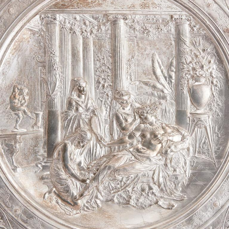The silver charger mounted on a velvet board, of circular form in the Neo-Grec manner, depicting a classical figural scene of a semi-clad maiden surrounded by three female attendants with an exotic colonnaded interior, within a florally decorated