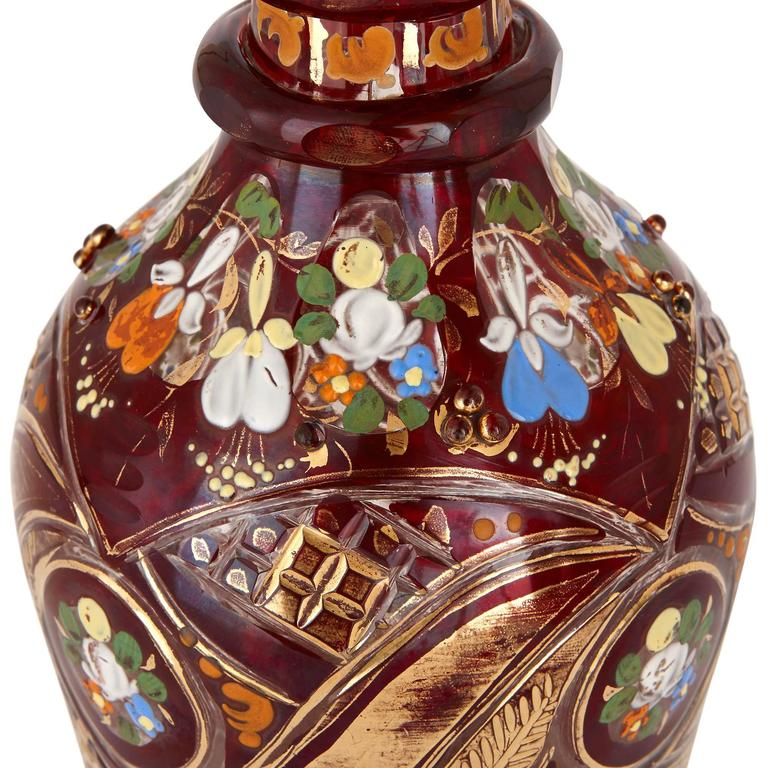 The decanter with octagonal ring knoped neck and faceted body and surmounted with a conical stopper, the ruby colored glass decorated throughout with painted flower bouquets and gilt highlights.  This opulent glass decanter exemplifies Bohemian