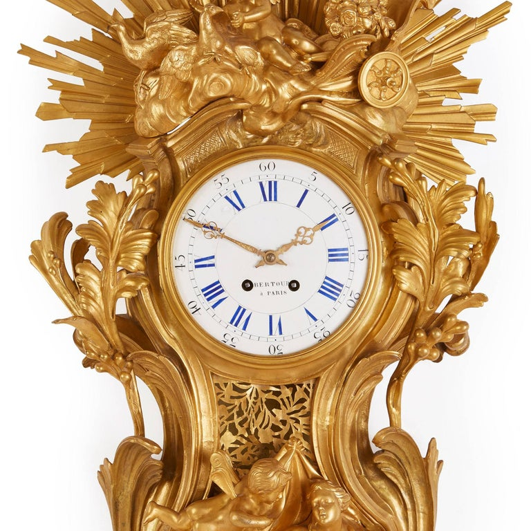 This beautiful Belle Époque style Cartel clock is notable for its stunning depiction of a sunburst, which is depicted in vivid golden gilt bronze. The central circular enamel dial is set within an elaborately detailed ormolu case depicting multiple
