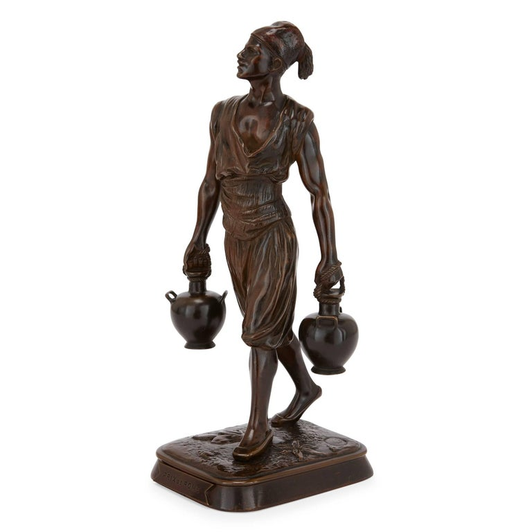 These charming antique Orientalist style figures were crafted by prestigious French makers Emile Pinedo (French, 1840-1916) and Marcel Debut (French, 1865-1933). One figure is modelled in the form of a Tunisian water carrier and the other is