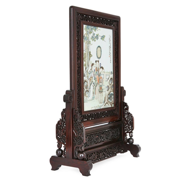 This exquisite Chinese screen is crafted from Hongmu, a dark rosewood from South East Asia. The ornately carved frame depicts dragons and scrolling foliate shapes. The central porcelain plaque depicts Chinese ladies in a detailed landscape with a