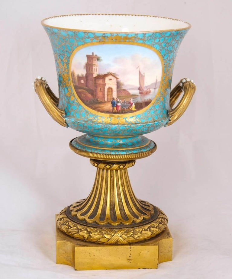 This elegant pair of vases have been mounted with gilt bronze and decorated in the style of the Sevres manufacturers. They were designed originally to be used as cachepots, or decorative containers for plants and their pots. They are bell-shaped, or