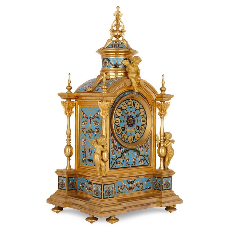 This exceptionally detailed clock set consists of a mantel clock and a pair of accompanying vases, which are all crafted in ormolu and extensively decorated in vibrant cloisonné enamel. The clock sits on ormolu toupie feet upon which is set the