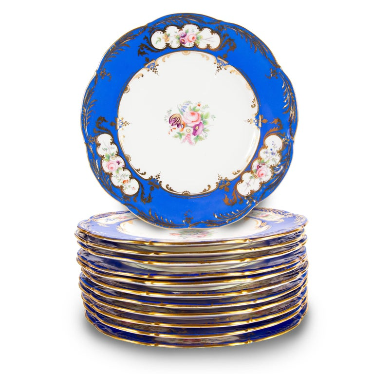 These blue and white porcelain dinner plates will make an excellent set, perfect for entertaining. They have been expertly made in a not-quite circular shape, with central floral decoration on white ground, surrounded by a royal blue rim. The rims