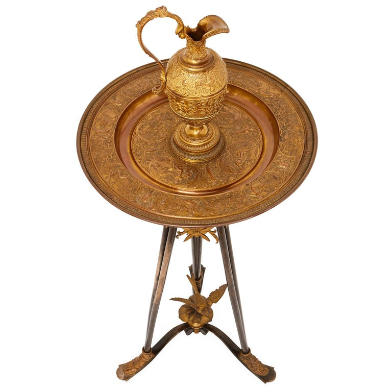 The exceptional bronze casting, in stunningly intricate detail, on this beautiful sculptural piece has been attributed to master metalworker Ferdinand Barbedienne. The piece takes the form of a bronze ewer on a large round basin platter and a tripod