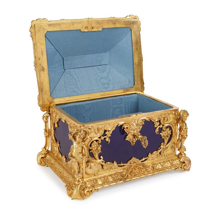Of rectangular form, the cobalt-blue ground porcelain plaques mounted with rich ormolu corner mounts with scrolls, floral bouquets and a grotesque mask escutcheon, the hinged cover topped with an ormolu cherub handle, on scroll feet, the porcelain