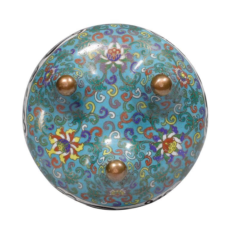 Made for the Persian market with Arabic inscriptions, decorated with lotus flowers on a turquoise ground, set on three feet.