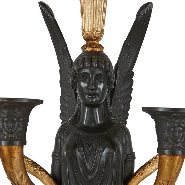 A pair of Empire gilt and patinated bronze candelabra. Each with a winged Victorian female figure carrying a torchère on their head and light arms to the side with a square shaped Giallo di Siena marble base.