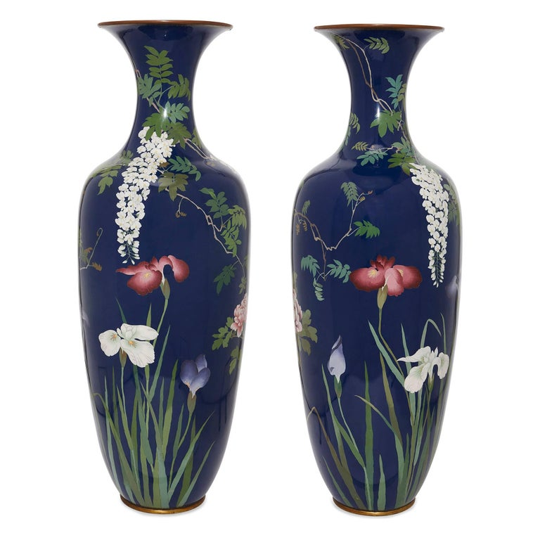 This pair of statuesque cloisonne enamel vases were made during the Japanese Meiji period in the late 19th century. The vases are ovoid in shape, and set with a blue ground. Their polished surfaces are adorned with foliate scenes of trees, birds and