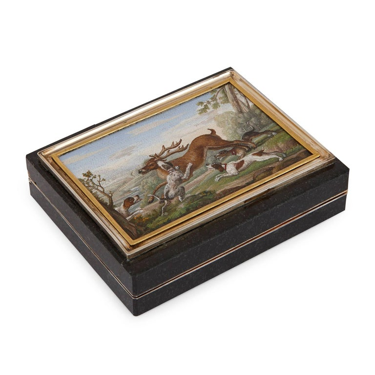 This antique Italian snuff box features a fine, micromosaic panel and silver gilt mounts. The micromosaic panel is set to the top of the box within a rectangular silver gilt frame. It depicts a hunting scene of a stag being chased and attacked by