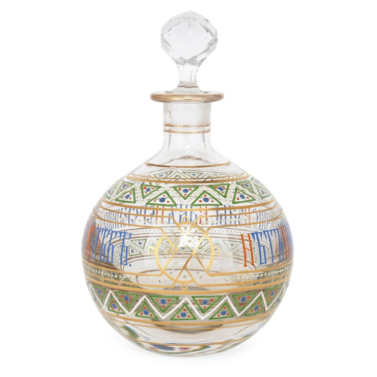 This humorous Russian antique vodka drinking set comprises six glass tumblers and one glass decanter. The decanter is of a bulbous shape, surmounted by a cut glass finial. The set is decorated all over with enameled geometric patterns in primary