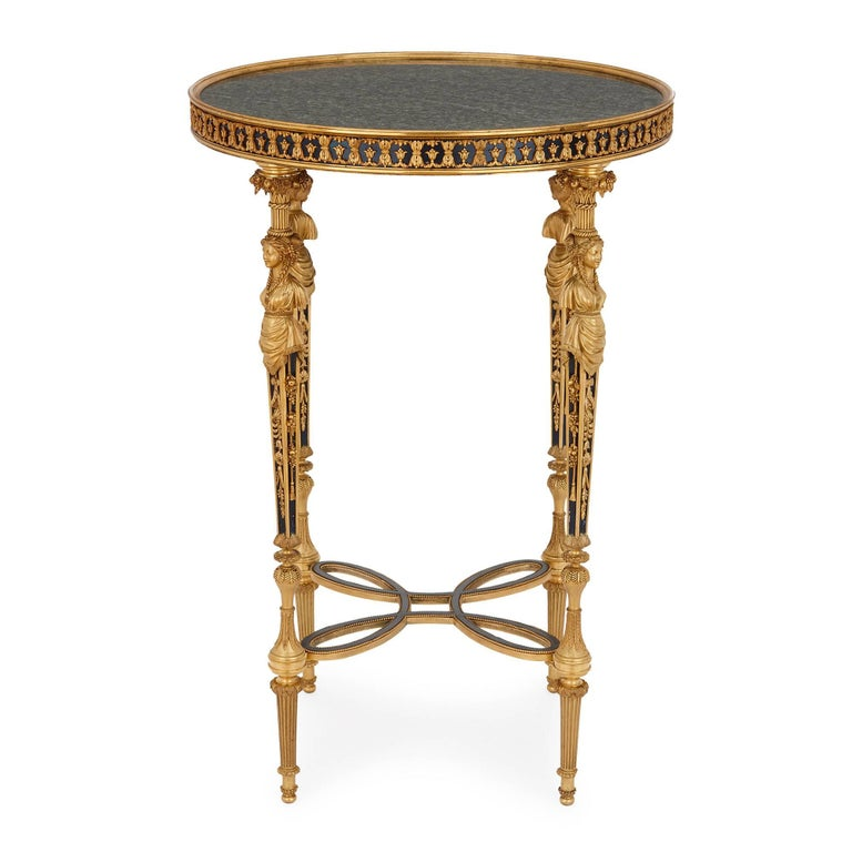 This refined and elegant round side table, or gueridon, has a circular top of green veined marble. Running around the edge of the top of the table is a band of tole, which is mounted with ormolu in a repeating floral pattern. The table top is set on