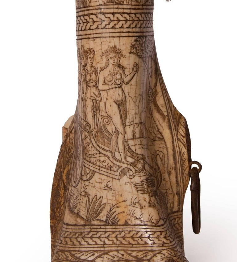 This curious antique powder box has been crafted from the femur bone of a mammal. The organically shaped box features carvings all over of mythological scenes inspired by ancient Greece and acanthus leaf and wheat patterns. The narrow, upper post