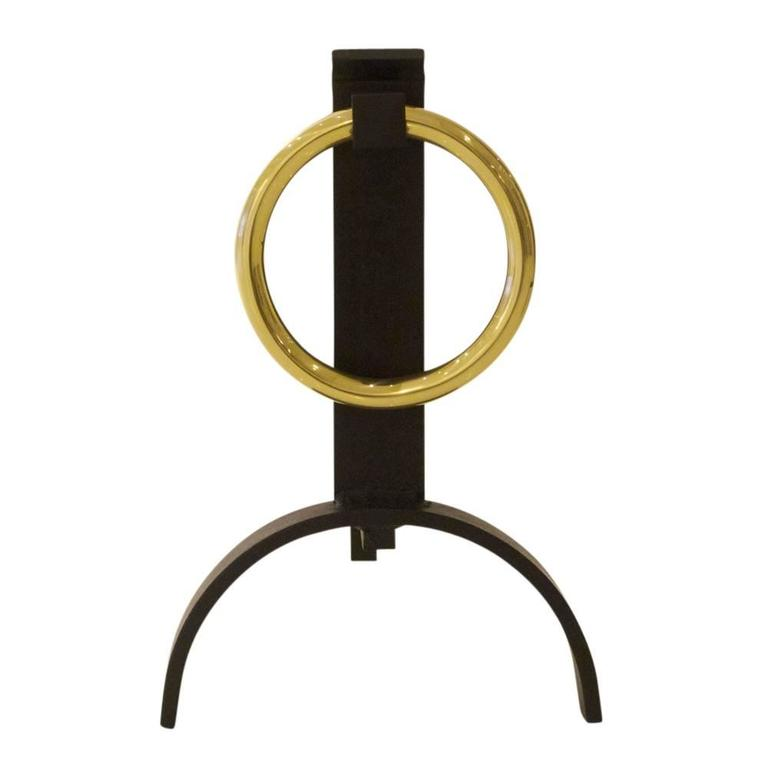 Donald Deskey style andirons brass buckle, USA, 1960s. Circular brass buckle motif andirons with arched base and wrought iron shanks. The brass buckle was re-finished and the iron elements were restored in matte black and then waxed.