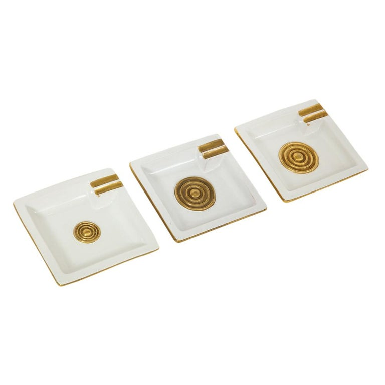 Zaccagnini ceramic ashtrays gold white medallion signed, Italy, 1950s. Set of three in good vintage condition with minute loss to each tray (photographed). Strong graphic pattern with gold medallion centre and gold glazed outlined cigarette rest.