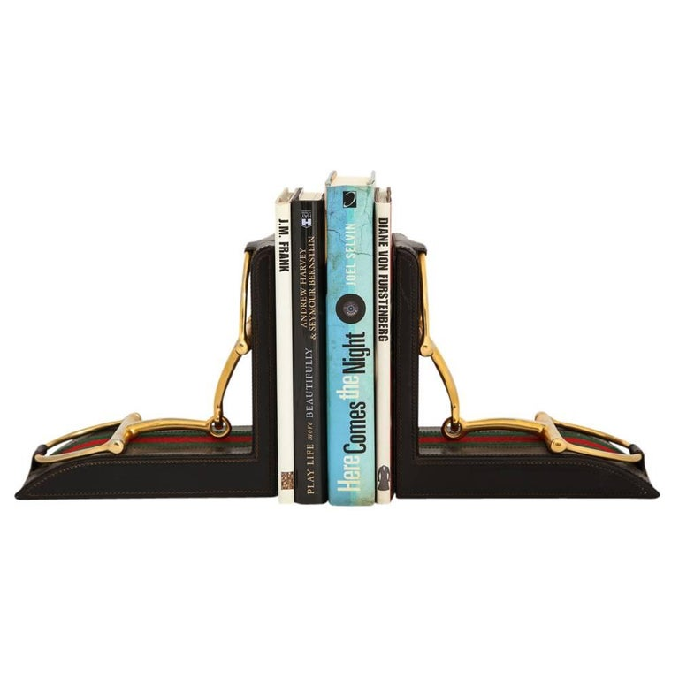 Gucci Horsebit Leather and Brass Bookends Signed Italy 1970's. Brass stirrups attached to the leather slings and mounted on the iconic Gucci green and red fabric which has been stitched on to the leather. Large scale bookends. Marked: