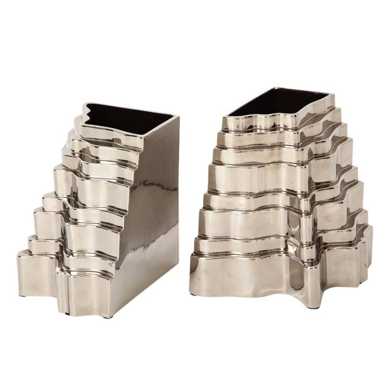 Sergio Asti Collina vases, ceramic, metallic silver chrome, signed. Two Collina (Hill in Italian) Series vases glazed metallic silver chrome. The vessels' design emulates a hill or grade with multiple graduated steps. Both vessels are signed with a