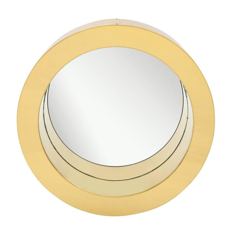 C. Jere porthole mirror, brass. Medium scale chunky round mirror with a warm patina to the original lacquered brass. Some scratching to brass finish and minor wear to the mirror. Has multiple hanging/display options on its original pebbled masonite