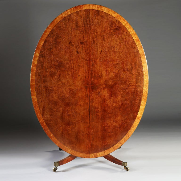 A large mahogany oval breakfast table with highly figured tilt top, including an inlaid border, resting on four fluted legs terminating in brass castors.