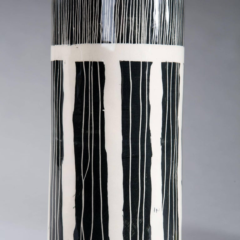 A pair of black and white Studio Pottery vases, with contrasting yellow bands, now converted as lamps.  Currently wired for the UK. Please enquire for rewiring services.  Please note: Lampshades not included.