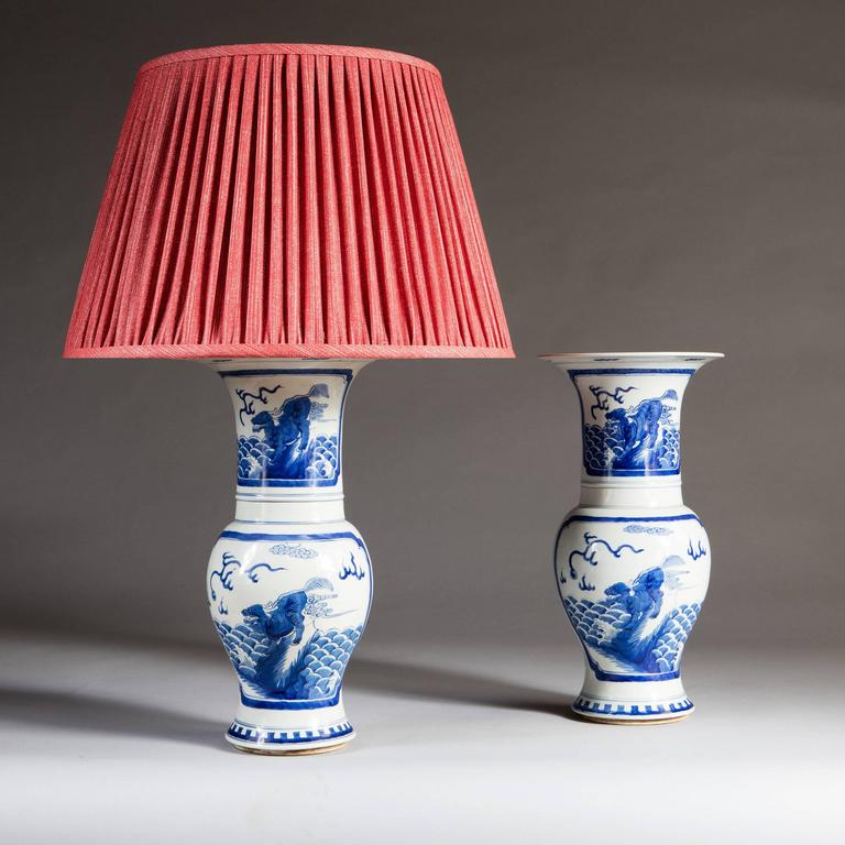 A pair of 20th century Chinese blue and white trumpet vases, decorated with cartouches depicting dragrons.  Please note: Lampshades not included.  Currently wired for the UK. Please enquire for rewiring services.