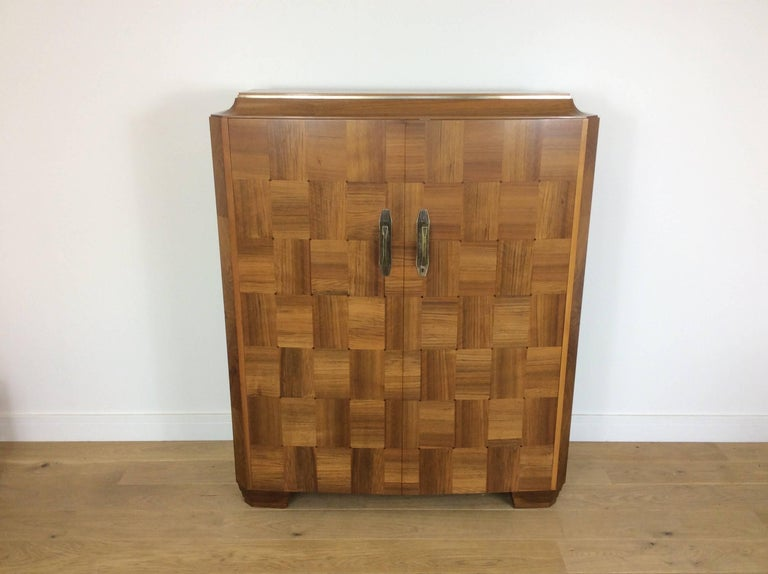 Art Deco Bureau cabinet with beautiful parquetry walnut doors, raised on stepped block feet, the top curving up with inlaid pewter band, bronze door handles, the interior pigeon holed for compartmental storage.