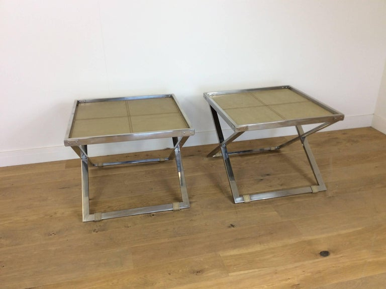 Mid-Century Modern design. A pair of midcentury X-frame butlers tables, thick heavy flat chrome frames with inset shagreen tops. Excellent quality to these designer tables French, circa 1960. Measure: 55 cm H, 70 cm sq.
