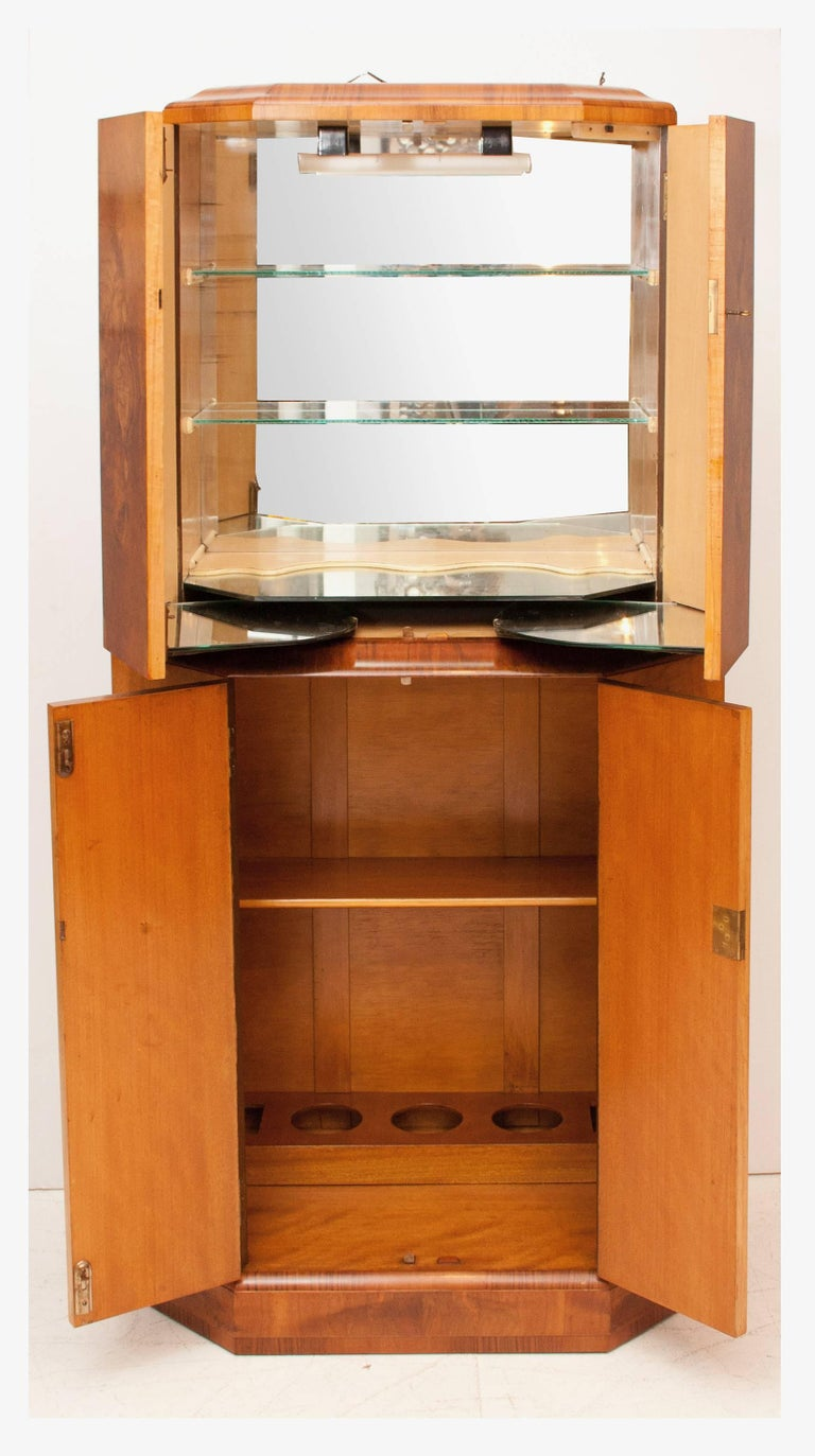 Art Deco cocktail bar Art Deco cocktail cabinet in a beautiful figured walnut. The top section opens to reveal mirrored interior, the lower section shelved and fitted for bottle storage. Measure: 166 cm H, 80 cm W, 44 cm D British, circa 1930.